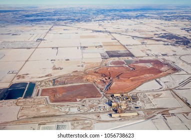 A potash mine surrounded by patchwork of agriculture fields and winding roads viewed from an airplane in a winter landscape in saskatchewan