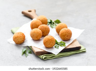 Potato balls croquettes with parsley on a wooden board on a light gray background