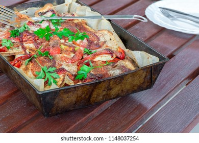 Potato, chicken and red pepper bake garnished with fresh parsley in baking tray on garden table