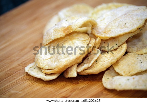 Potato chip crisps on a wooden board