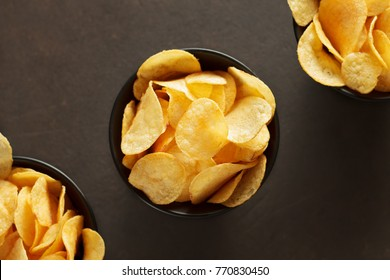 Potato chips in black bowls on brown background. Unhealthy vegan fast food. Top view with copy space.