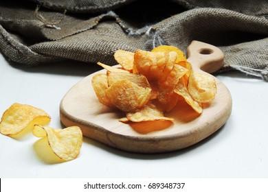 Potato chips in bowl and fresh potato