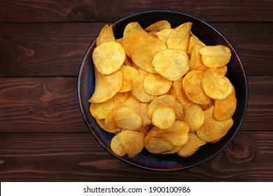 Potato chips in bowl on a wooden background, top view.