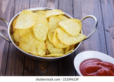 Potato chips in bowl on wooden background. Selective focus, horizontal.