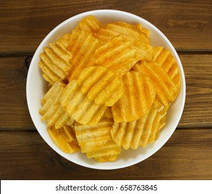 Potato chips in bowl on a wooden background, top view