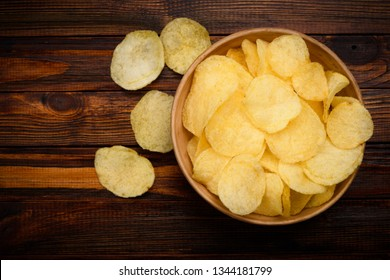 Potato chips in ceramic bowl on dark wooden table