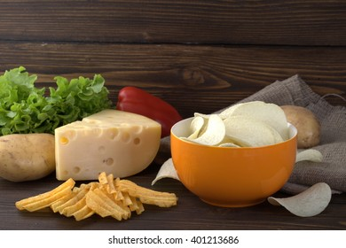Potato chips, cheese, if you cut the slices. In the background, red peppers, raw potatoes, and greens. All this in a home style on wooden background. Natural products