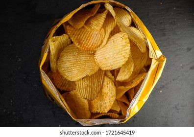 Potato chips or crisps isolated on a black stone background. Close-up of potato chips or crisps. Food background.