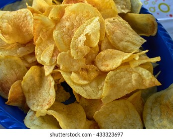 Potato chips crisps in served on a blue plate taken in closeup