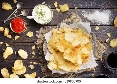 Potato chips with dipping sauces on a rustic table. Photographed from directly above.