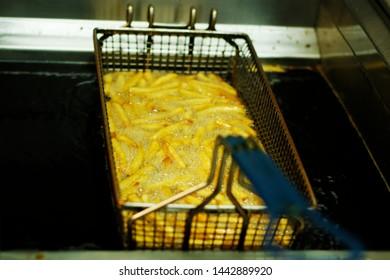 potato chips frying  in a deep fat fryer