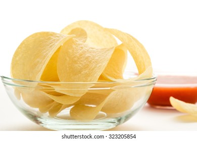 potato chips in a glass bowl on a white table with tomato dip
