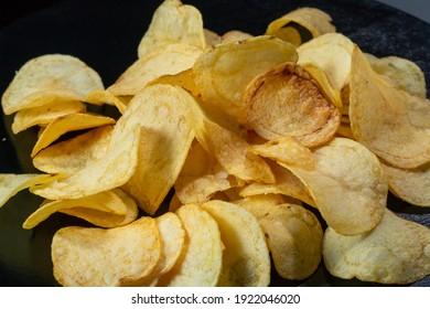 Potato chips on a black background close-up