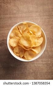 Potato chips on wood background