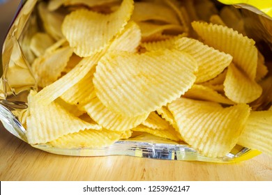 potato chips open bag on wood table