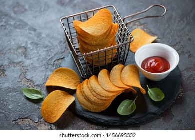Potato chips with paprika and dipping sauce on a stone slate, studio shot over brown stone background