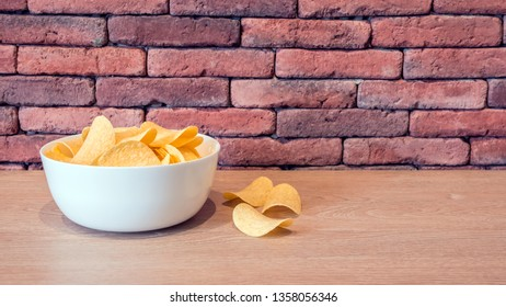 Potato chips in a white bowl, brick wall background