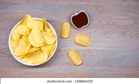 Potato chips in a white bowl, ketchup on the side, view from above