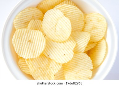Potato chips in the white bowl on white background