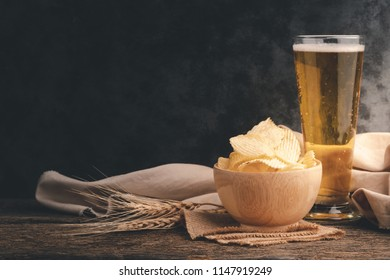 Potato chips in a wooden bowl with cold beer in a long glass on wooden table