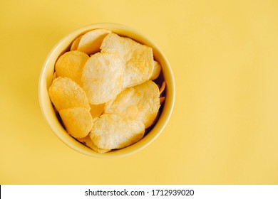 Potato chips in a yellow bowl on a yellow background. Top view. Copy, empty space for text