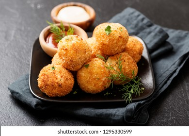 Potato croquettes - mashed potatoes balls breaded and deep fried, served with different sauce.