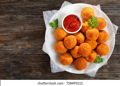 potato croquettes - mashed potatoes balls breaded and deep fried, served with tomato sauce on plate on old dark wooden table, view from above