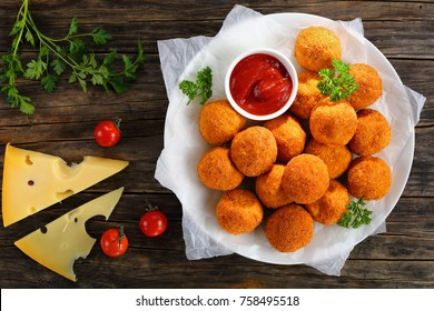 potato croquettes - mashed potatoes balls breaded and deep fried, served with ketchup on plate on old dark wooden table with tomatoes and cheese slices at background, view from above, close-up