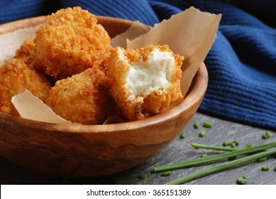 Potato croquettes in wooden bowl with fresh chives on slate cutting board. Closeup with selective focus on opened croquette.