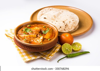 Potato curry or aloo or Aaloo masala fry with green peas, indian main course food served with flat bread also known as chapati or Roti, selective focus