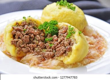 Potato dumplings stuffed with minced meat and served with sauerkraut (German name is Fleischknödel mit Sauerkraut)
