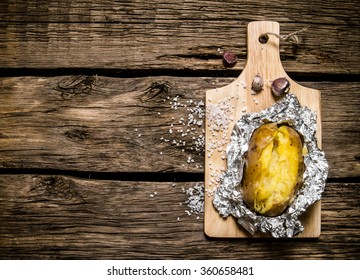 Potato food . Baked potatoes in foil on a wooden table . Top view