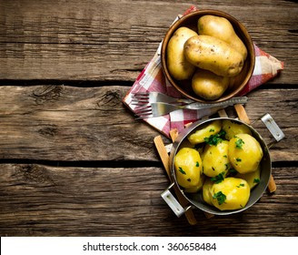 Potato food . Boiled potatoes with herbs on wooden table . Free space for text. Top view