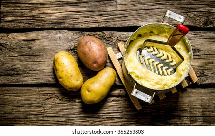 Potato food . Cooking mashed potatoes with pestle on wooden background. Top view