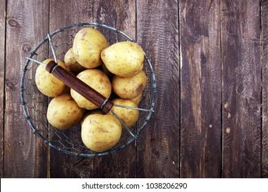 potato food . Fresh raw organic potatoes on old vintage background