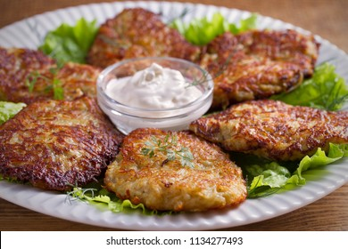 Potato fritters, latkes, draniki, hash browns - popular dish in many countries. Vegetable pancakes on white plate, wooden table. horizontal