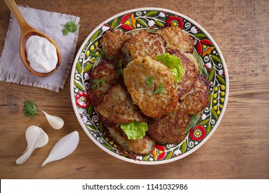 Potato fritters, latkes, draniki, hash browns. Vegetable pancakes on a plate, wooden table. horizontal, overhead