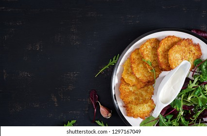 Potato fritters/draniki/pancakes served with sour cream. European cuisine. Kosher eating. Vegan food. Top view, flat lay, copy space