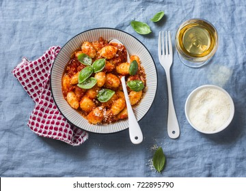 Potato gnocchi in tomato sauce with basil and parmesan and a glass of white wine on blue background, top view. Italian cuisine. Vegetarian food