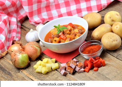 Potato goulash with sausage, pepper, onion and garlic on wooden table