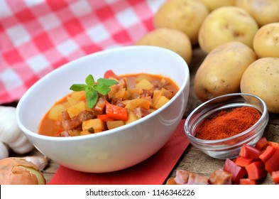 Potato goulash with sausage in white bowl, pepper, onion and garlic on wooden table