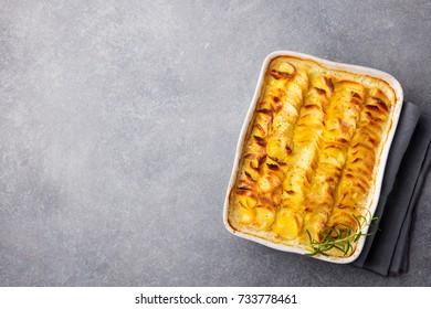 Potato gratin, backed potato slices with creamy sauce. Top view. Copy space.