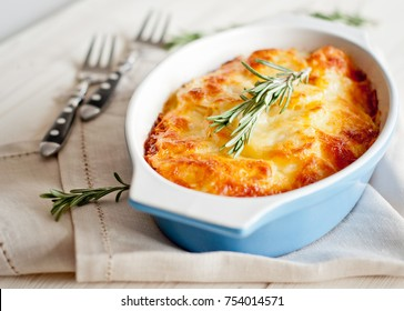 Potato gratin (baked potatoes with cream and cheese) with rosemary and forks on white table