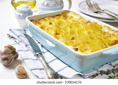 Potato gratin in a blue baking dish on a light background.