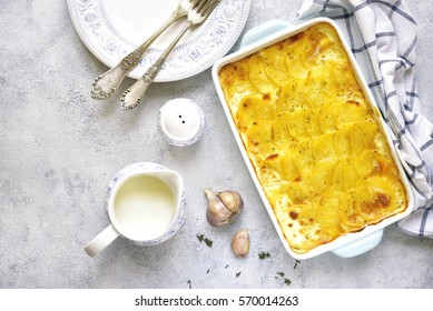 Potato gratin in a blue baking dish on a light background.Top view.