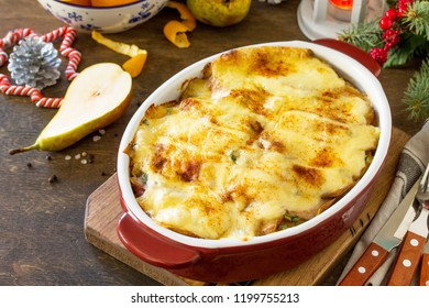 Potato gratin with pear, raclette cheese, and bacon on a festive Christmas table.Traditional french cuisine. Copy space.