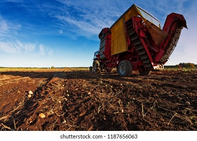 Potato harvesting machine has been attached to an old tractor on the autumn fields of the rural Finland. It's harvest time and the farmers are busy on their fields.