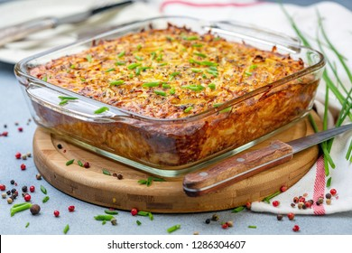 Potato kugel a traditional jewish dish in a glass pan on a wooden serving board, selective focus.