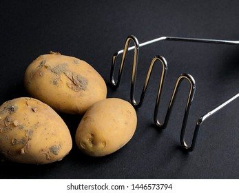 potato masher on black background with raw potato. Fresh organic potatoes on black background. Top view