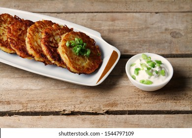 Potato Pancakes, Hash Browns, Latkes, Draniki On Wooden Table With Sour Cream. Flat Lay With Copy Space.